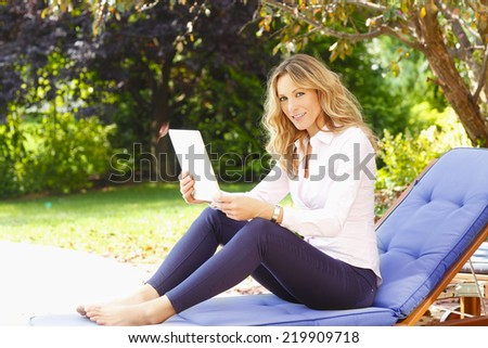 Modern casual woman relaxing at home while using digital tablet.  - stock photo