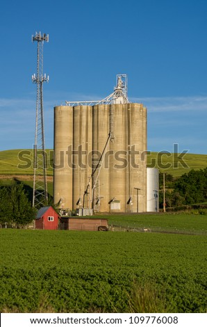 Modern cell tower and old grain elevator or silo - stock photo