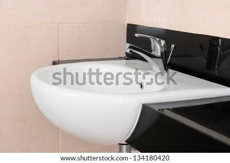 Modern ceramic hand wash basin with chrome water mixer tap in hotel washroom interior - stock photo