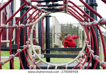 Modern children playground with rope tunnel, child playing in the background. - stock photo