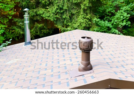 Modern chimneys on the roof of house