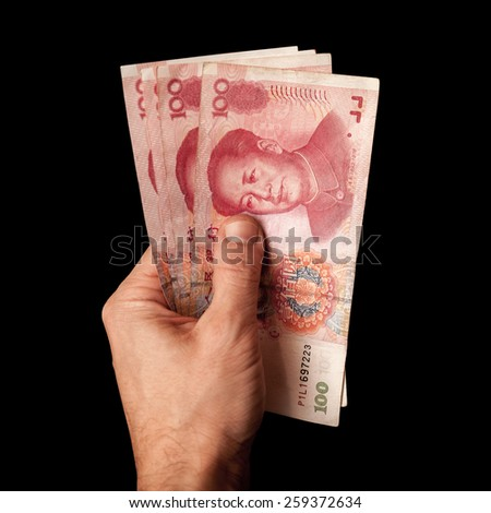 Modern Chinese 100 yuan renminbi banknotes in male hand isolated on black - stock photo