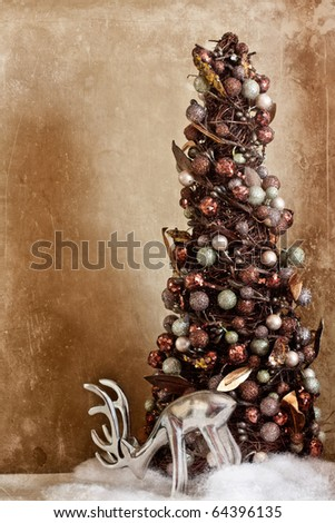 Modern christmas tree with bulbs and silver reindeer in the snow with vintage textured overlay. - stock photo