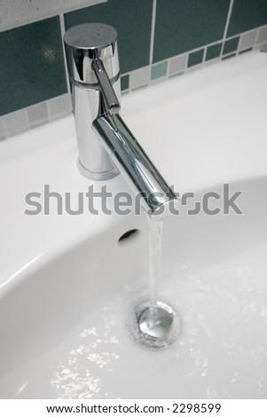 modern chrome tap in a green bathroom - stock photo