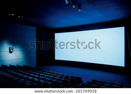 Modern cinema auditorium with white blank screen and luxury seats - dark movie theatre ready for projection - stock photo
