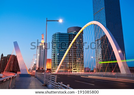 Modern city highway arc bridge night landscape of car light trails - stock photo