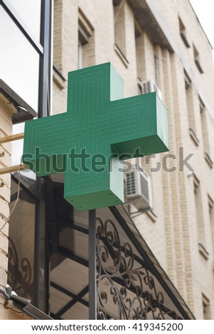 Modern city. Pharmacy. Signboard. Green LED cross. - stock photo