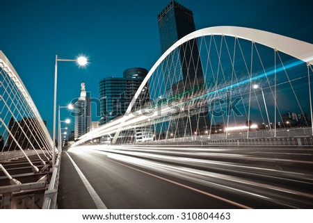 Modern city road arc ironbridge night landscape of car light trails in Tianjing