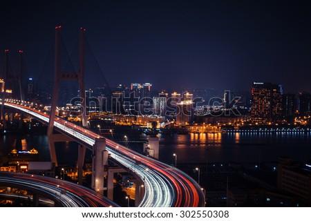 Modern city traffic road at night. Transport road junction on the bridge. - stock photo