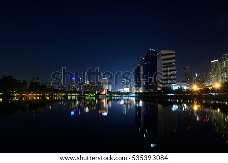 Modern city view of Bangkok, Thailand. Cityscape with Commercial Building Beside Lake in Public Park with Reflection at Twilight or Night