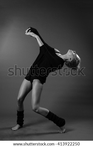 Modern classical theme: beautiful girl dancing sensual dance in a studio on a gray background, black and white photo