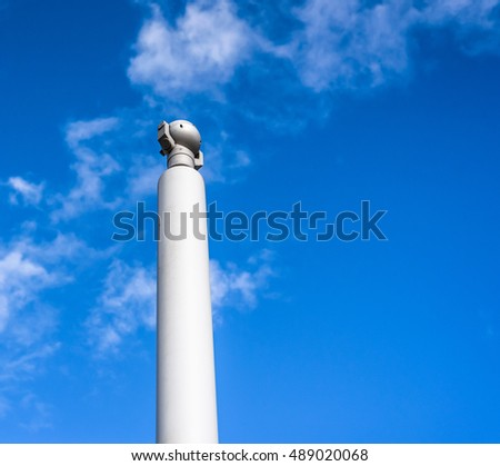 Modern closed circuit tv camera isolated against a blue sky.