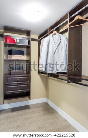 Modern closet in apartment building with boxes and clothes hung neatly. - stock photo
