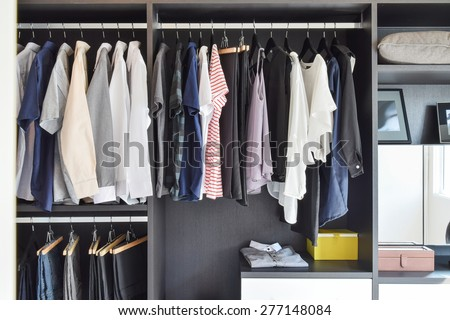 modern closet with row of cloths hanging in black wardrobe - stock photo
