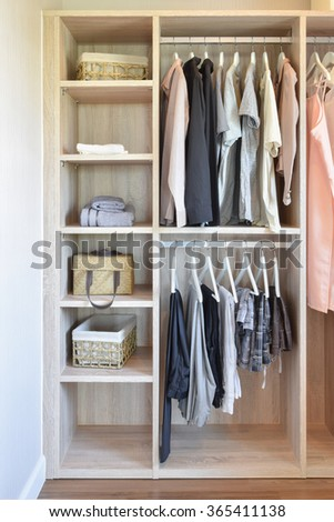modern closet with row of cloths hanging in wooden wardrobe - stock photo