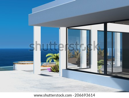 Modern coastal home with an outdoor patio overlooking the ocean on a hot tropical sunny day - stock photo