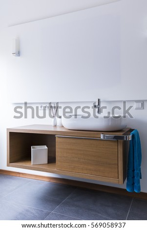 Modern comfortable bathroom with washbasin and wooden cabinets with utensils and towel