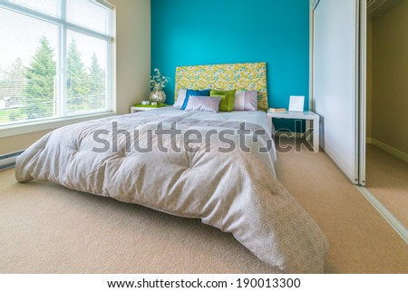 Modern comfortable, nicely decorated children bedroom painted in blue and the tray with the tea, coffee set on the bed. Interior design. - stock photo
