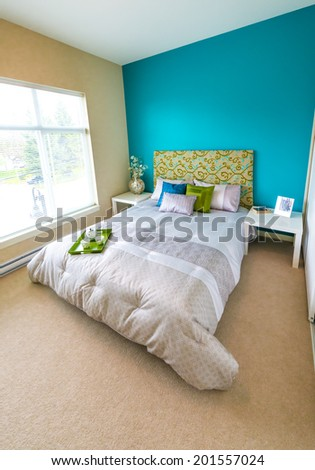 Modern comfortable, nicely decorated master, children bedroom painted in blue, and tray with the tea, coffee set on the bed. Interior design. Vertical. - stock photo