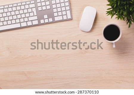 Modern computer keyboard, white mouse, mug of coffee and green plant on bright wooden office desk. - stock photo