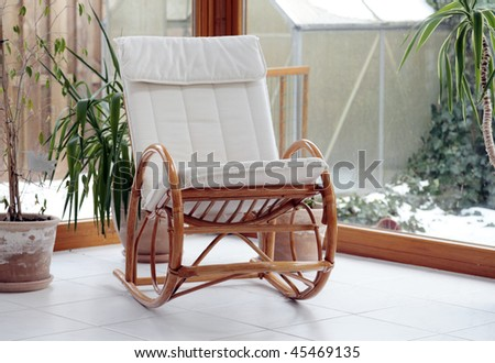 modern conservatory with a rocking chair - stock photo