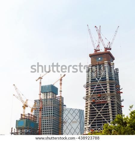 Modern construction. Crane building a new skyscraper. - stock photo