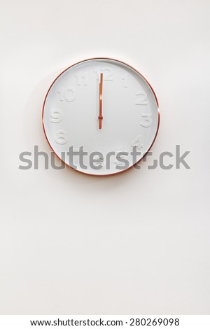 Modern copper and white decorative wall clock on a white wall - stock photo