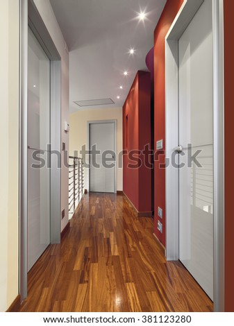 modern corridor with wood floor and red walls - stock photo