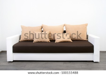 modern couch at white wall - stock photo
