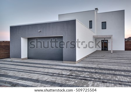 Modern country house with gray-white facade on the sky background. Around the house there is a tiled area and a wooden fence. Outside. Horizontal.
