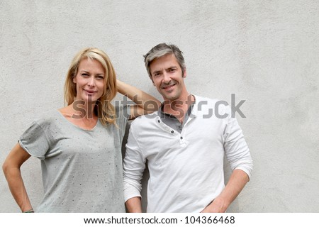 Modern couple standing on concrete wall - stock photo