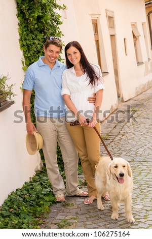 Modern couple with Labrador dog in romantic city smiling together