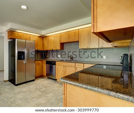 Modern day kitchen with beige tile floor and grey accents. - stock photo