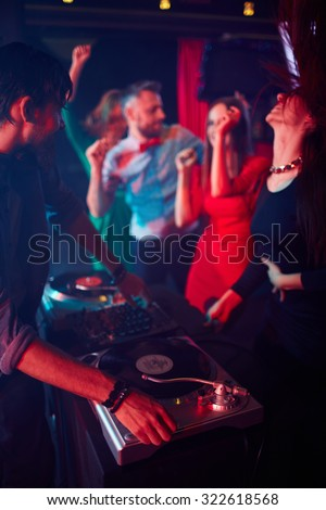 Modern deejay adjusting sound on turntables and looking at dancing girls - stock photo