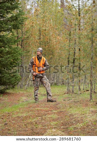 modern deer hunter standing in forest - stock photo