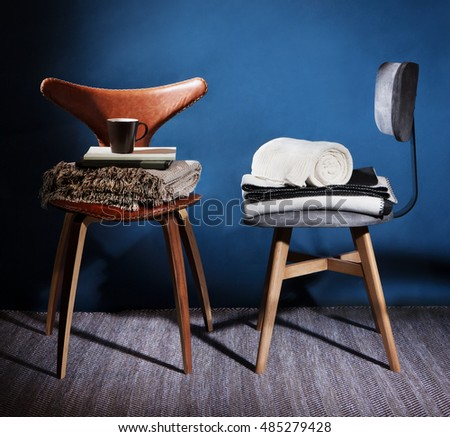 modern design chairs on studio concept photo with beautiful shadows blankets books a nd a cup