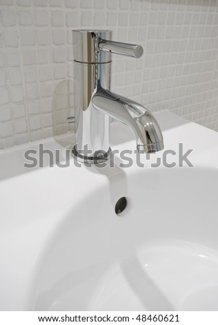 modern design chrome water mixer tap over white ceramic sink - stock photo