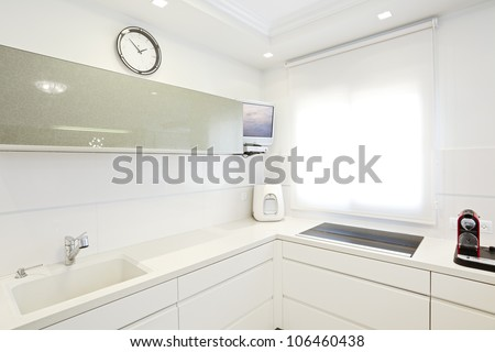 Modern design kitchen with white elements Note to reviewer: Original picture in the TV Screen  was replaced by one of my images. - stock photo