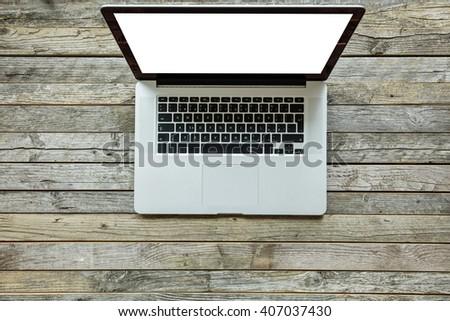 Modern designed laptop on old wooden desk - stock photo