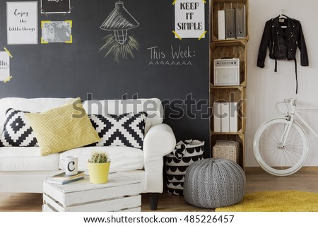 Modern Designed Room Interior With A Black Wall Motivational Posters On White Couch