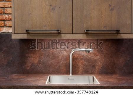 Modern designer chrome water tap over stainless steel kitchen sink. - stock photo