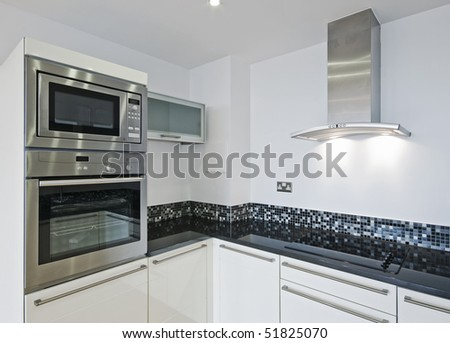 modern designer kitchen with electric appliances stone worktop and mosaic tiles - stock photo