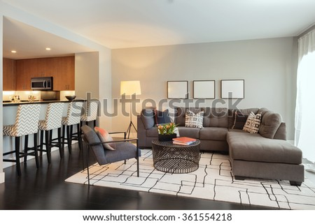 Modern designer living room with couch, copy space for art, bar chairs and adjacent kitchen. - stock photo