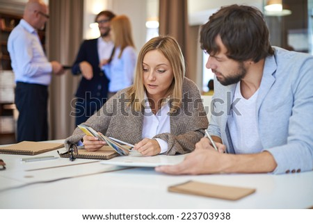 Modern designers in casual discussing color palette in working environment - stock photo