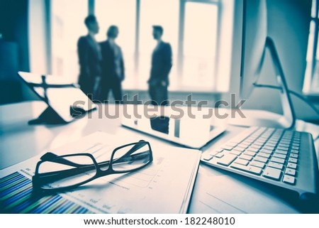 Modern devices, documents, eyeglasses on the foreground, unrecognized businessmen on the background  - stock photo