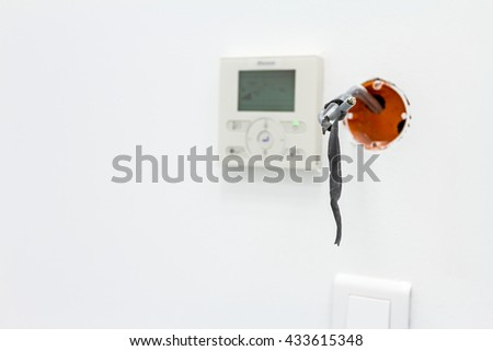 Modern digital electronic thermostat, climate control system in background. Unfinished electrical or system outlet, socket, plug in. Exposed wiring in an unfinished plug socket - stock photo