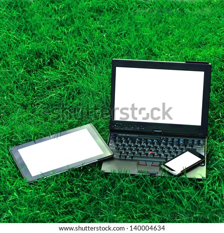 Modern digital tablet PC with mobile smartphone and  laptop on green grass - stock photo