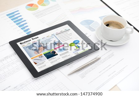 Modern digital tablet with business media website on a screen lying on a desk with some papers and documents, pen and cup of coffee. - stock photo