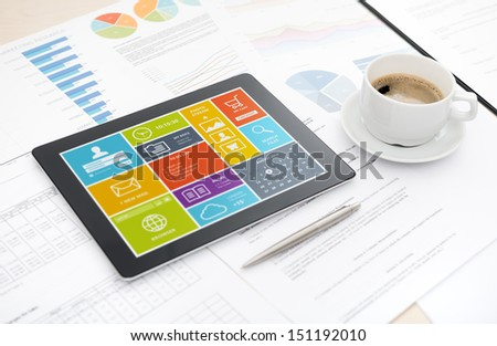 Modern digital tablet with colorful modern widows user interface on a screen lying on a desk with some papers and documents, pen and cup of coffee. - stock photo