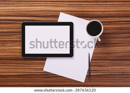 Modern digital tablet with empty screen, paper, pen and cup of coffee on dark wooden office desk.